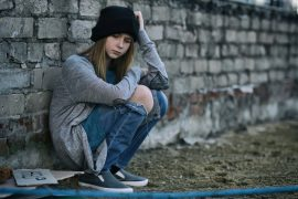 girl sits alone outside